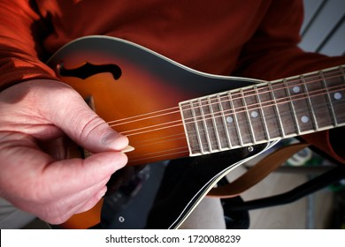 A man plays his Eight string mandolin at home during lock down - Shutterstock ID 1720088239
