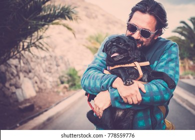 man plays with his pug puppy dog