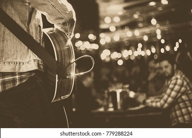 Man plays live music with his guitar in a cafe.