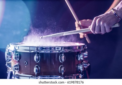 man plays musical percussion instrument with sticks closeup on a black background, a musical concept with the working drum, beautiful lighting on the stage - Shutterstock ID 619878176