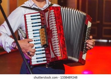 A man plays a red accordion. Musical instrument.  The event at the restaurant. Black and white keys. Hand harmonica.