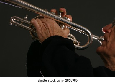 Man plays silver trumpet with back-lighting