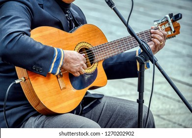 A man plays Spanish Guitar in a street in Barcelona