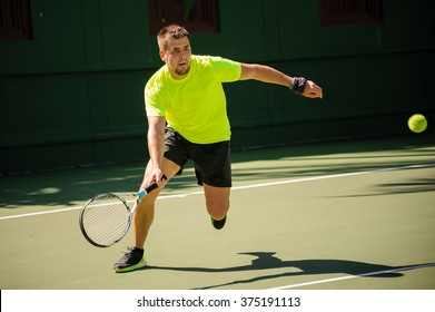 Man plays tennis in bright cloth  on  the court