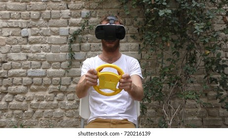 A man plays virtual augmented reality game using head mounted display and a motion sensing steering wheel.