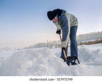 Man plowing his backyard with shovel after heavy snowing