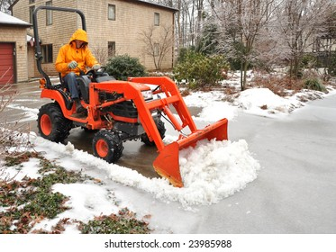 Man plowing snow and ice from a suburban driveway