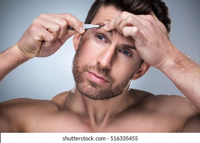 Man plucking eyebrows with tweezers