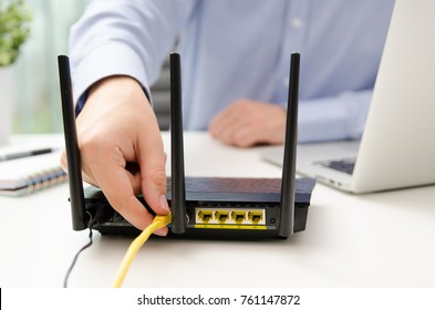 Man plugs Ethernet cable into router. router wireless wire broadband home office cable plug concept