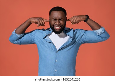 Man plugs his ears with hands for not hear anymore. Photo of african man in casual outfit on coral background.