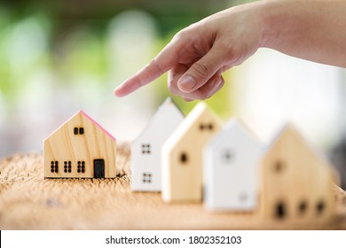 Man point finger for select a home model on the wood on sunlight, in the public park, Loan for real estate or saving money for buy a new house to family in the future concept.