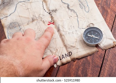 Man point into Ancient (fake hand draw) vintage crumpled paper with Not Real map of Pirates with Treasure mark cross and compass. Not real place in the map.