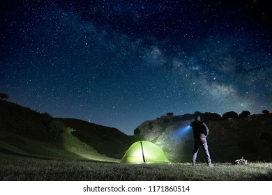 man pointing blue flashlight to mountain below starry sky in Nebrodi Park, Sicily