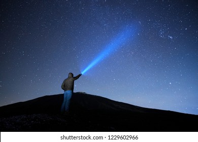 man pointing blue flashlight to starry sky in Etna Park, Sicily