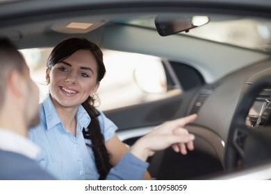 Man pointing a car interior while sitting in a car