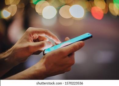 Man pointing finger on screen smartphone on background illumination glow bokeh light in night city