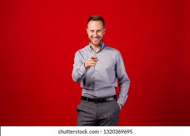 man pointing finger at you over red background. emotion and people concept.
