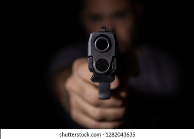 Man Pointing a Handgun at the Camera - Low-Key Photography with Dark Black Background