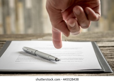 Man pointing his finger to a typed document with a pen lying on top of it as he requests signature, close up view of his hand and paperwork.