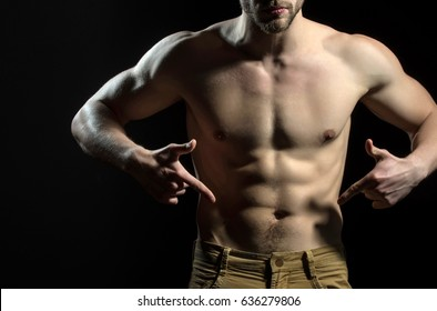 Man is pointing his fingers at his groin in jeans. Figure of athlete, naked male torso. The power of man. Male genitals or penis. Confident young guy
