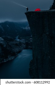 A man is pointing his flashlight into the dark night sky while standing on the edge of Preikestolen above a fjord, near Stavanger, Rogaland, Norway.