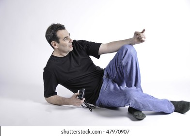 Man is pointing and holding a light meter while he is on the floor with a seemless background.