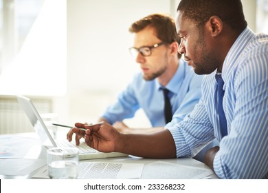 Man pointing at laptop for his colleague