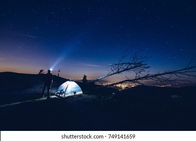 Man pointing light from his flashlight to the sky. Night camp in mountains. Starry night