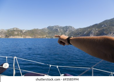 A man is pointing the montains on the boat. He has bracelets