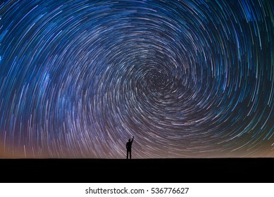 Man Pointing North in a spiral star trail