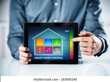 Man pointing to an online interface for a smart house with a control panel with icons for lighting, temperature, security, wireless, power and an eco energy chart
