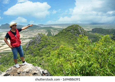 A man is pointing out on the mountain with nature background at National Park in Prachuap Khiri Khun Province on April 5th, 2020 in Thailand.