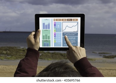 Man pointing at touchscreen and analyzing marketing statistics on his digital tablet