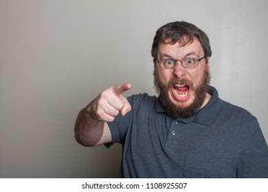 Man pointing while yelling in the direction of the camera