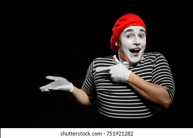 Man points a finger at something imaginary on his hand. Waist up portrait of male mime with broad smile, isolated on black.