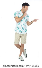 Man points his fingers to the side. He made a decision. Brazilian male wearing a Hawaiian style floral shirt and beige shorts. Summer, tropical.