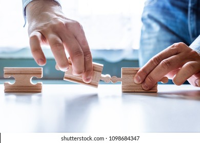 The man points to the same two incompatible jigsaw puzzles. The concept of misunderstanding, non-conforming elements, mutually exclusive statements.