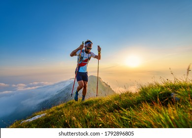 Man with poles in the mountains with sunset behind