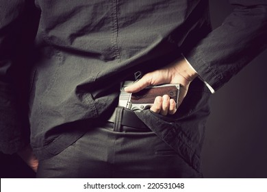 A man, policeman or gangster concealing his gun behind his back