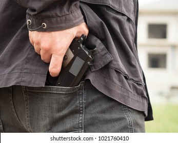 A man, policeman or robber, gangster concealing his gun behind his back