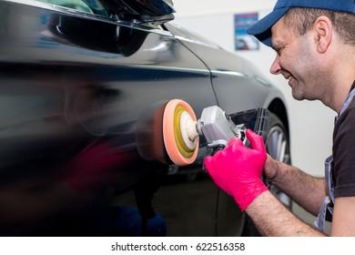 A man polishes a black car with a polishing machine