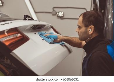 A man polishes a white machine with a polishing machine