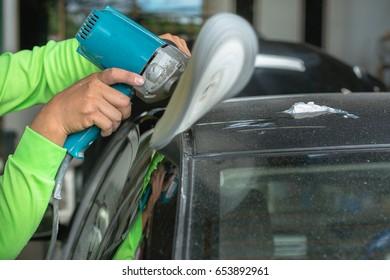 A man polishing a black car with a polishing machine