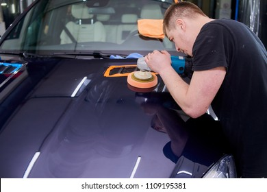 A man is polishing a blue car. Polishing machine and polishing paste for gloss.