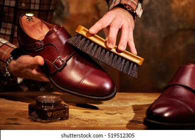 Man polishing leather shoes with brush.