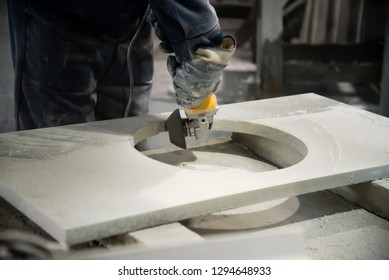 Man polishing marble stone table by small angle grinder. Stone cutter