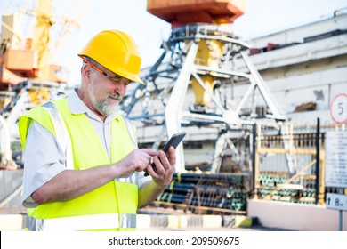 man in the port works on the tablet