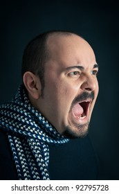 Man portrait with angry expression on dark background.