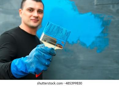 Man portrait blur smiling work painter hold paintbrush with blue paint.