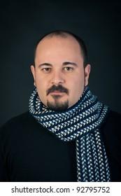 Man portrait with confident expression on dark background.